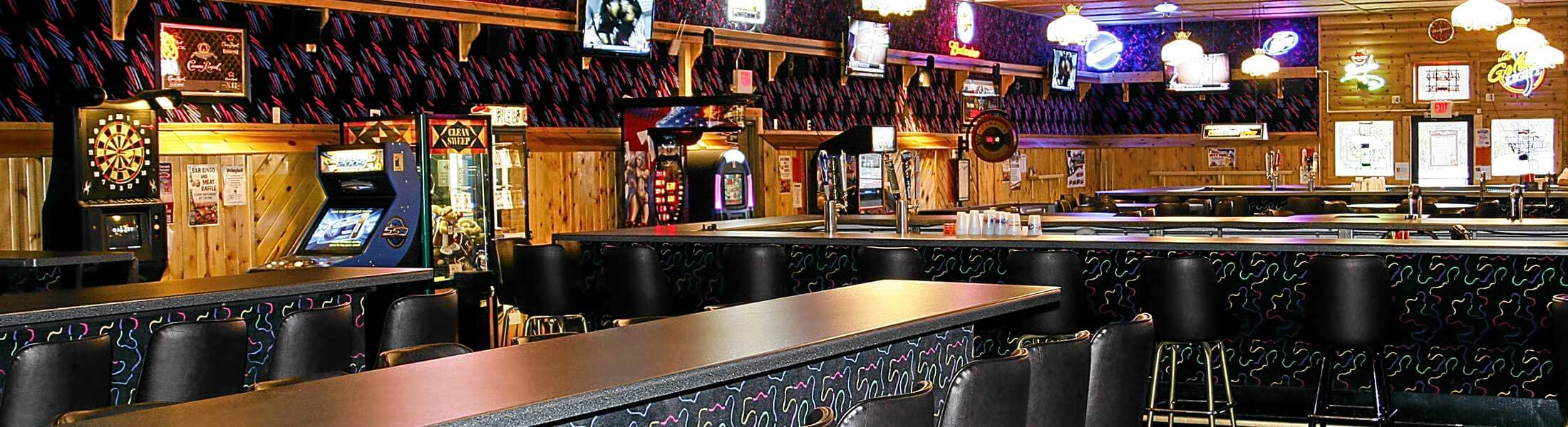 Horseshoe bar and high-top tables inside Main Gate Bar & Grill in Little Falls, MN