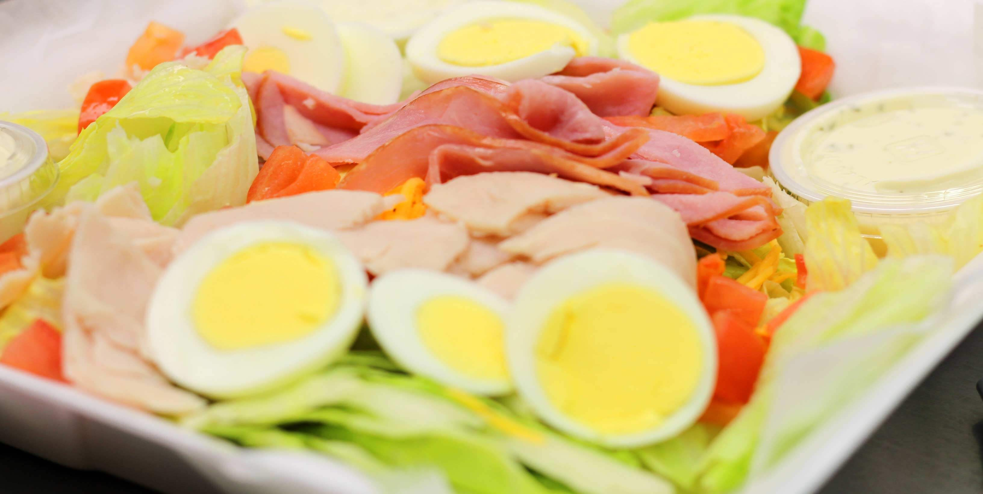 Cheif salad made up of sliced eggs, turkey, ham, bacon and lettuce