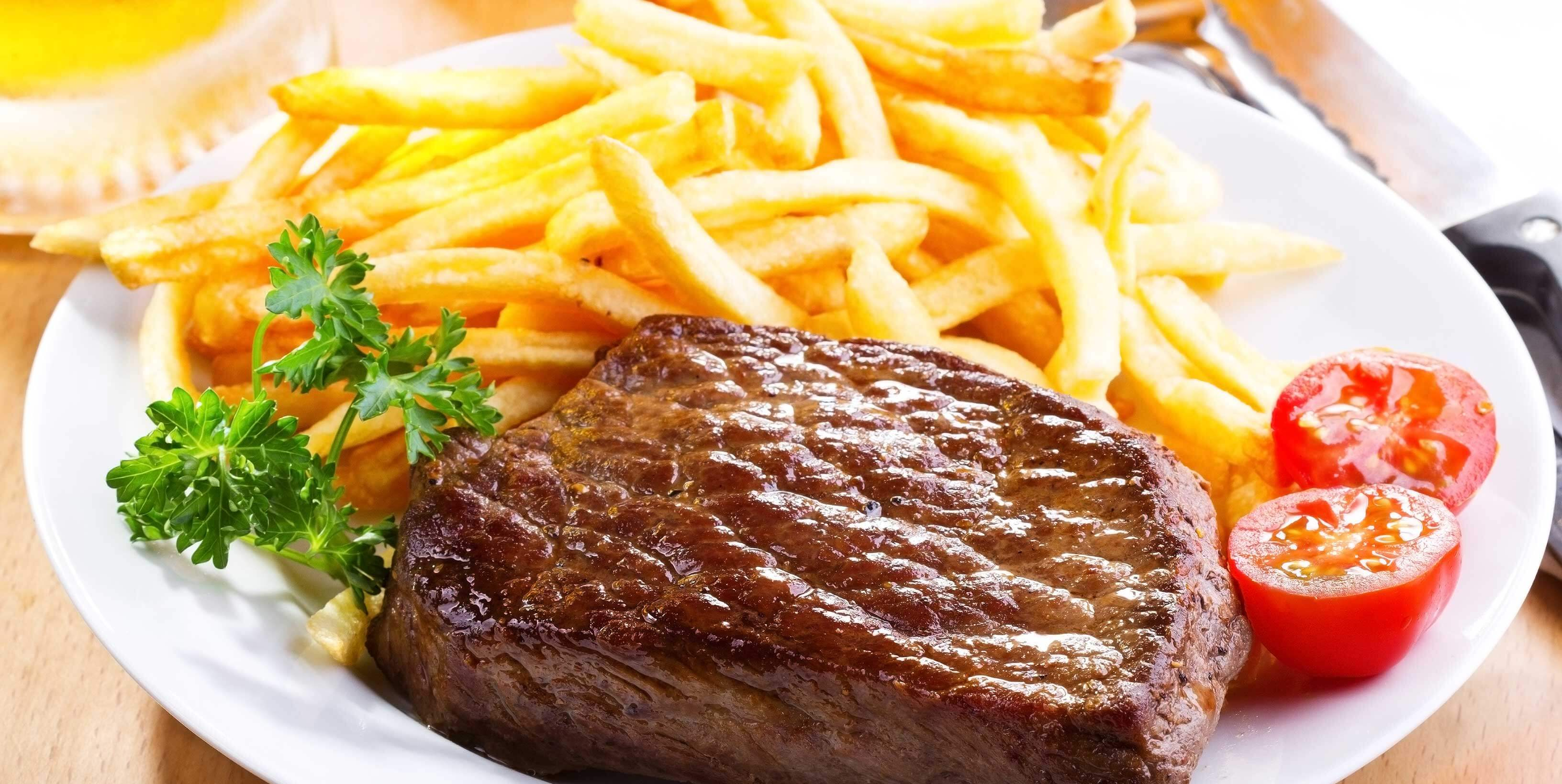Plate of grilled steak and golden deep fried French Fries